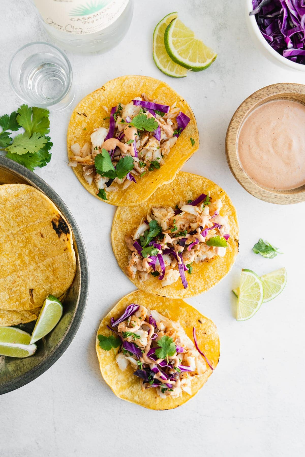 fish tacos on a white table with chipotle mayo and slaw