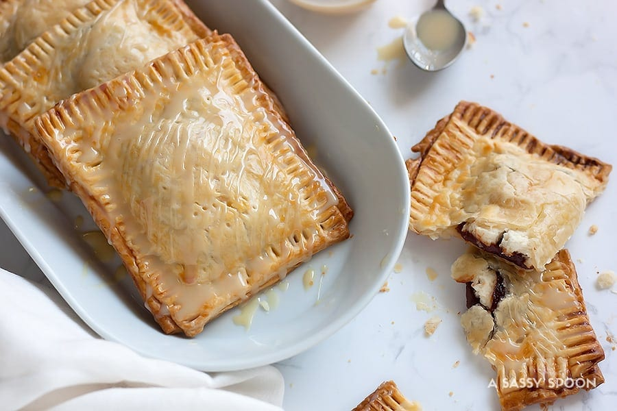 These semi-homemade guava and cream cheese pop tarts are super easy to make using refrigerated pie crust and condensed milk for drizzling. The perfect combination of a Cuban treat on an American classic.
