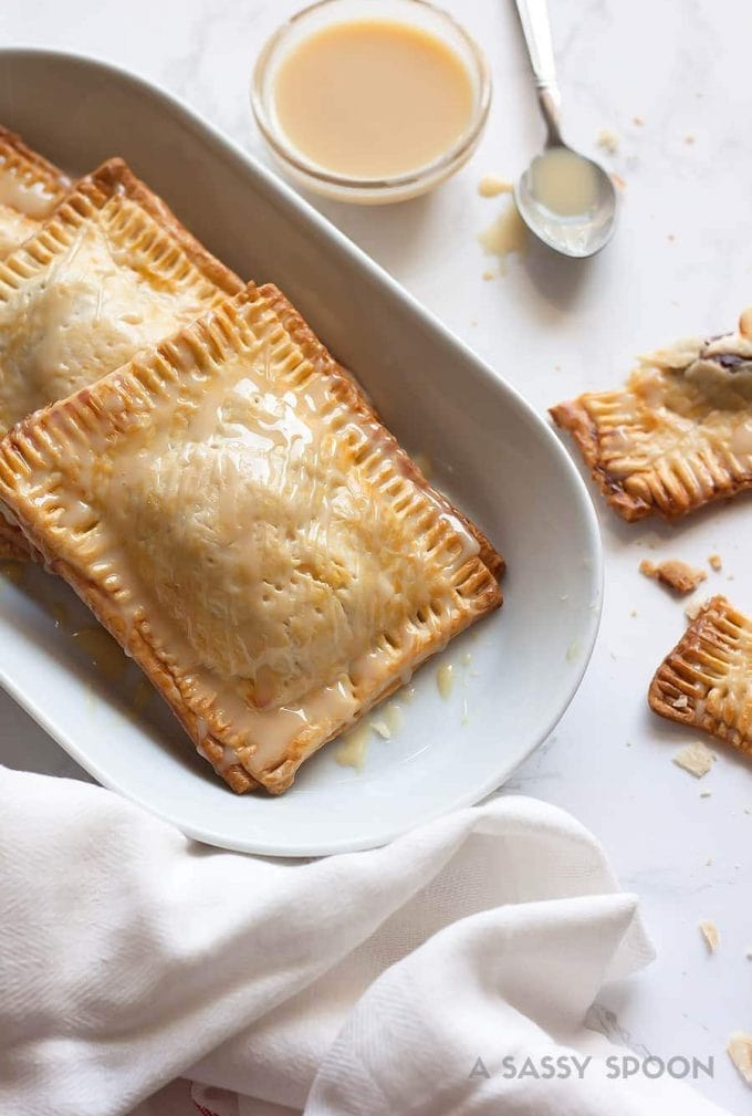 Super easy, semi-homemade guava and cream cheese pop tarts made using refrigerated pie crust then topped with a drizzle of condensed milk. The perfect combination of a Cuban treat on an American classic.