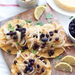 Using leftovers or shredded rotisserie chicken, make these Crispy Chicken Tacos, vaca frita style, topped with sautéed onions and black beans!