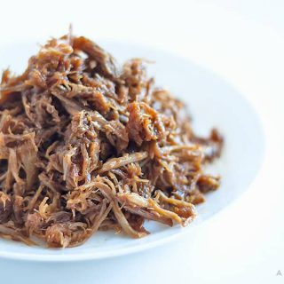 Sweet, boozy, easy-to-make homemade honey whiskey barbecue sauce on top of smokey, slow cooked shredded pulled pork. Practically cooks itself!