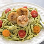 Zucchini noodles topped with a avocado sauce and seared scallops
