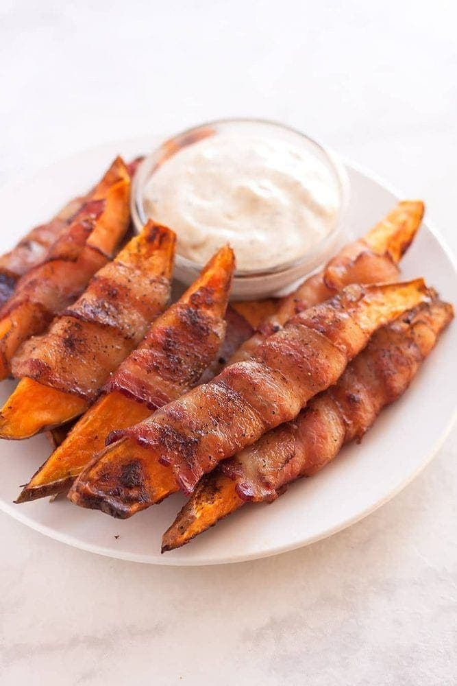 Sweet potatoes cut into fries, seasoned with salt, pepper, and smoked paprika, then wrapped in uncured applewood smoked bacon and baked to perfection!