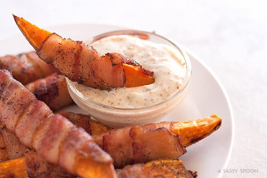 Sweet potatoes cut into fries, seasoned with salt, pepper, and smoked paprika then wrapped in bacon and baked to perfection. Best appetizer everrr!