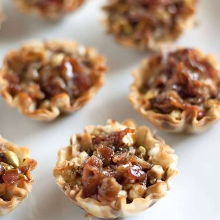Mini phyllo cups filled with basil, garlic, creamy goat cheese, chopped pistachios, and crumbled applewood smoked bacon then topped with a honey-balsamic glaze.