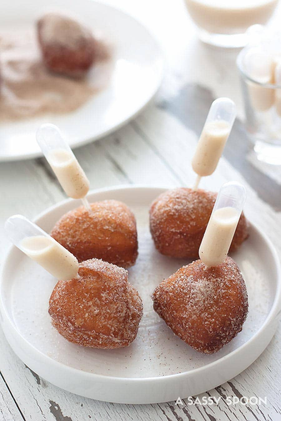 Quick and easy-to-make donut holes made in just minutes using refrigerated biscuit dough with a pipette of homemade coquito aka Puerto Rican eggnog!