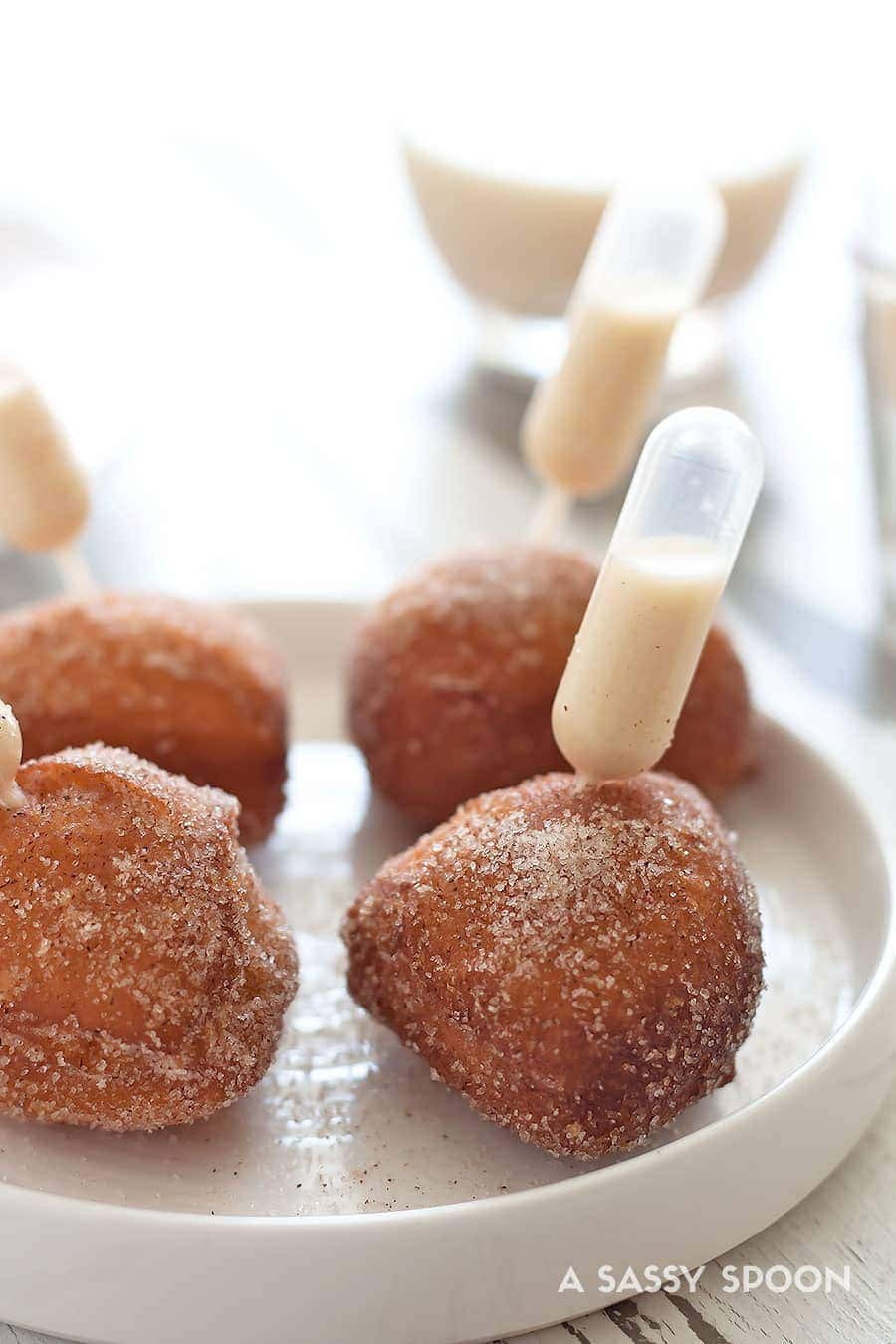Donut holes with an eggnog-filled pipette