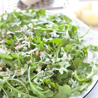 A simple 6-ingredient spicy arugula salad made with peppery arugula, shaved Pecorino cheese, pine nuts, red chili flakes, lemon juice and olive oil! Makes for a perfect starter or side.