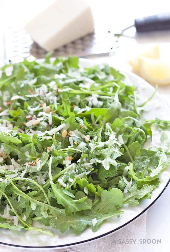 a plate of arugula with pine nuts, lemon dressing, red chili flakes and pecorino