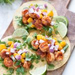 Jerk Shrimp Tacos with Mango Salsa. Spicy jerk shrimp paired with a refreshing mango salsa on corn tortillas! Perfect for any day of the week!