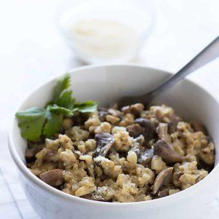 Cauliflower mushroom risotto served in white bowl