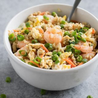 Forget takeout. MakeCauliflower Shrimp Fried Rice at home using riced cauliflower, carrots, peas, onions, garlic, and coconut aminos in just 15 minutes!