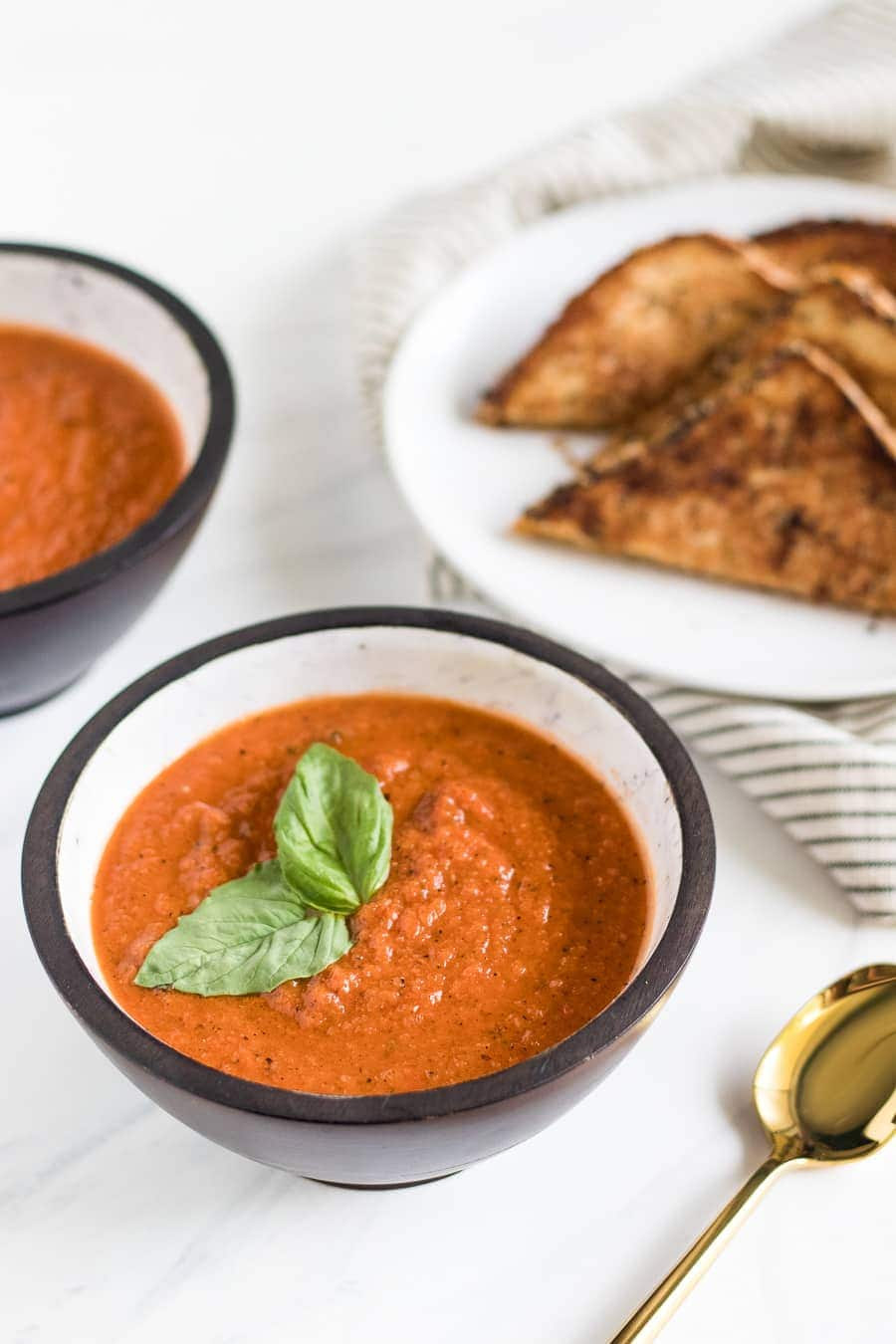 A deliciously simple homemade roasted tomato basil soup that you can enjoy all year round with a melty grilled cheese made with Irish whiskey butter!