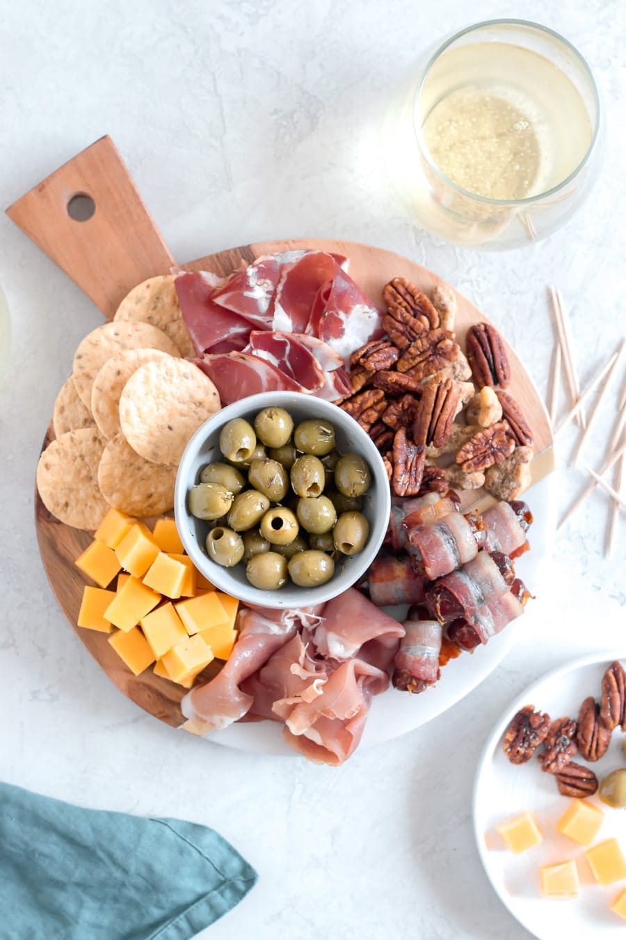A beautiful cheese board is always impressive. Take it next level by simply adding bacon wrapped dates, marinated olives, and candied mixed nuts!