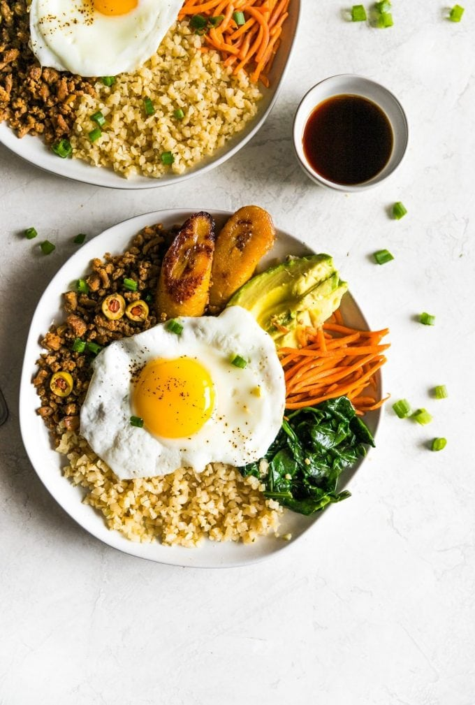 Inspired by Korean bibimbap, this healthy-ish Cuban bibimbap bowl has ground turkey (picadillo), seasoned cauliflower rice, sautéed garlic spinach, carrots, avocado, and sweet plantains. Colorful, flavorful and delicious!