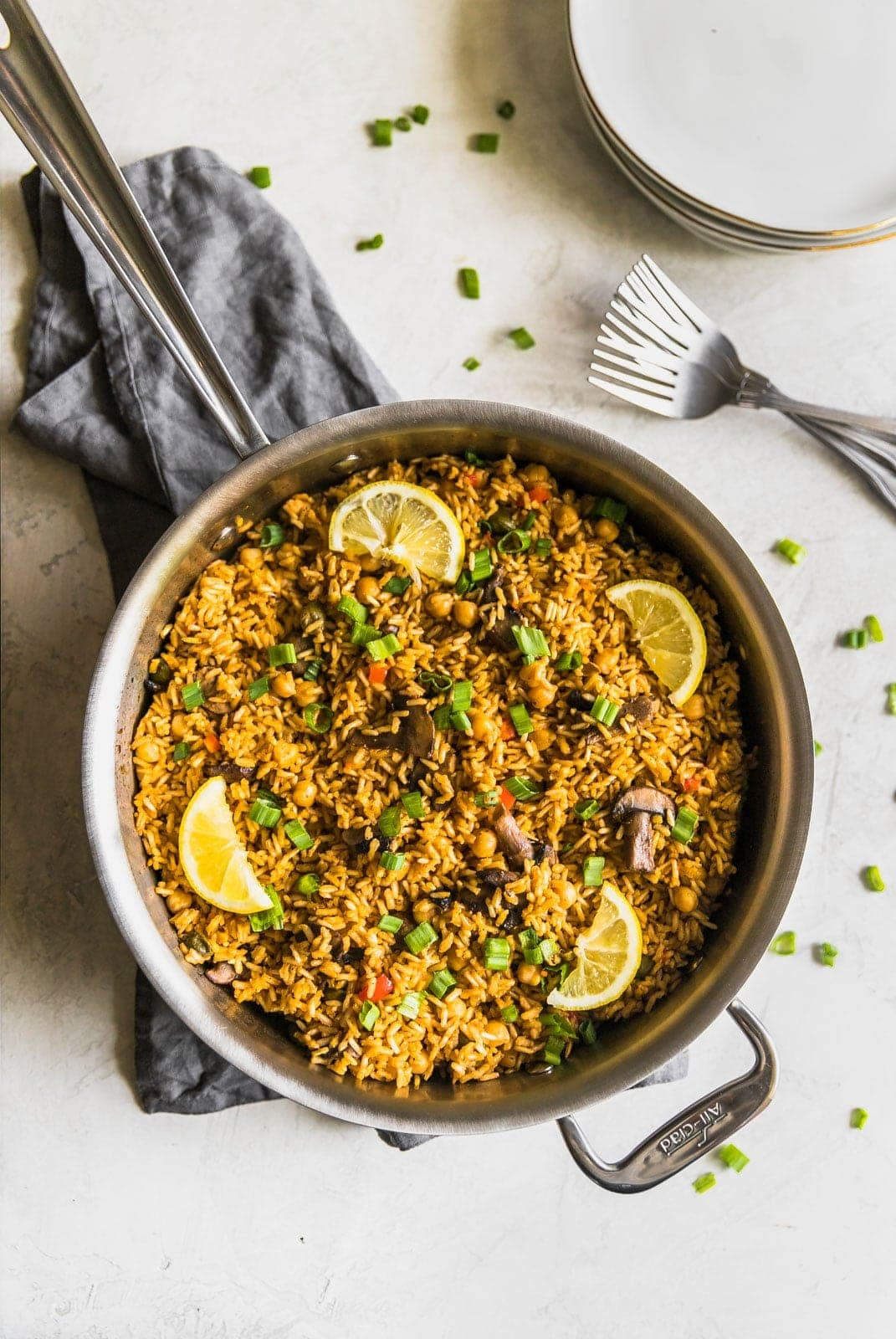 A quick and easy vegetarian paella made with brown rice, garbanzo beans, mushrooms, red peppers, and peas. Perfect weeknight meal!