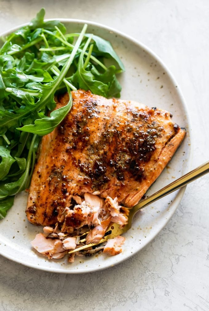 honey mustard salmon broken in pieces on a speckled plate with arugula salad