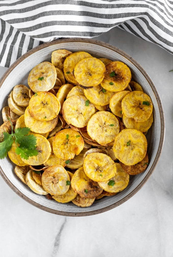 Crispy, salty, baked plantain chips with a vegan garlic dip. The perfect paleo, dairy-free, vegan snack made with just 5-ingredients!