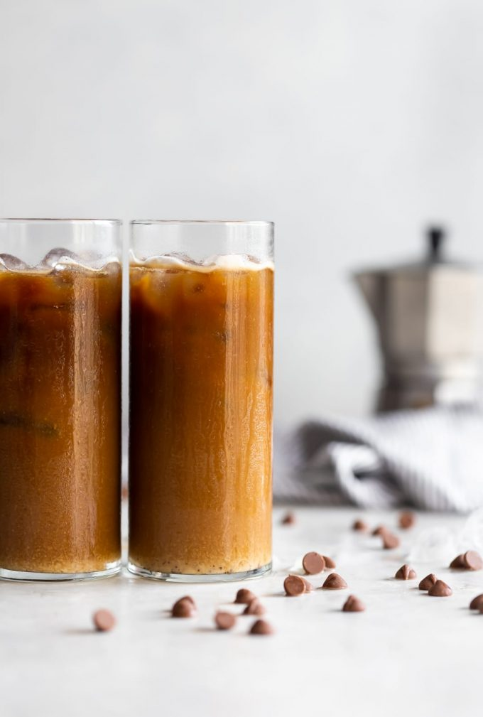 A frothy dairy-free iced cafe con leche (milk with coffee drink) made with sweetened Cuban coffee, chocolate chips, hazelnut creamer, and almond milk.