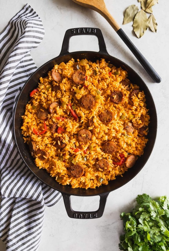 large skillet with chicken sausage and yellow rice