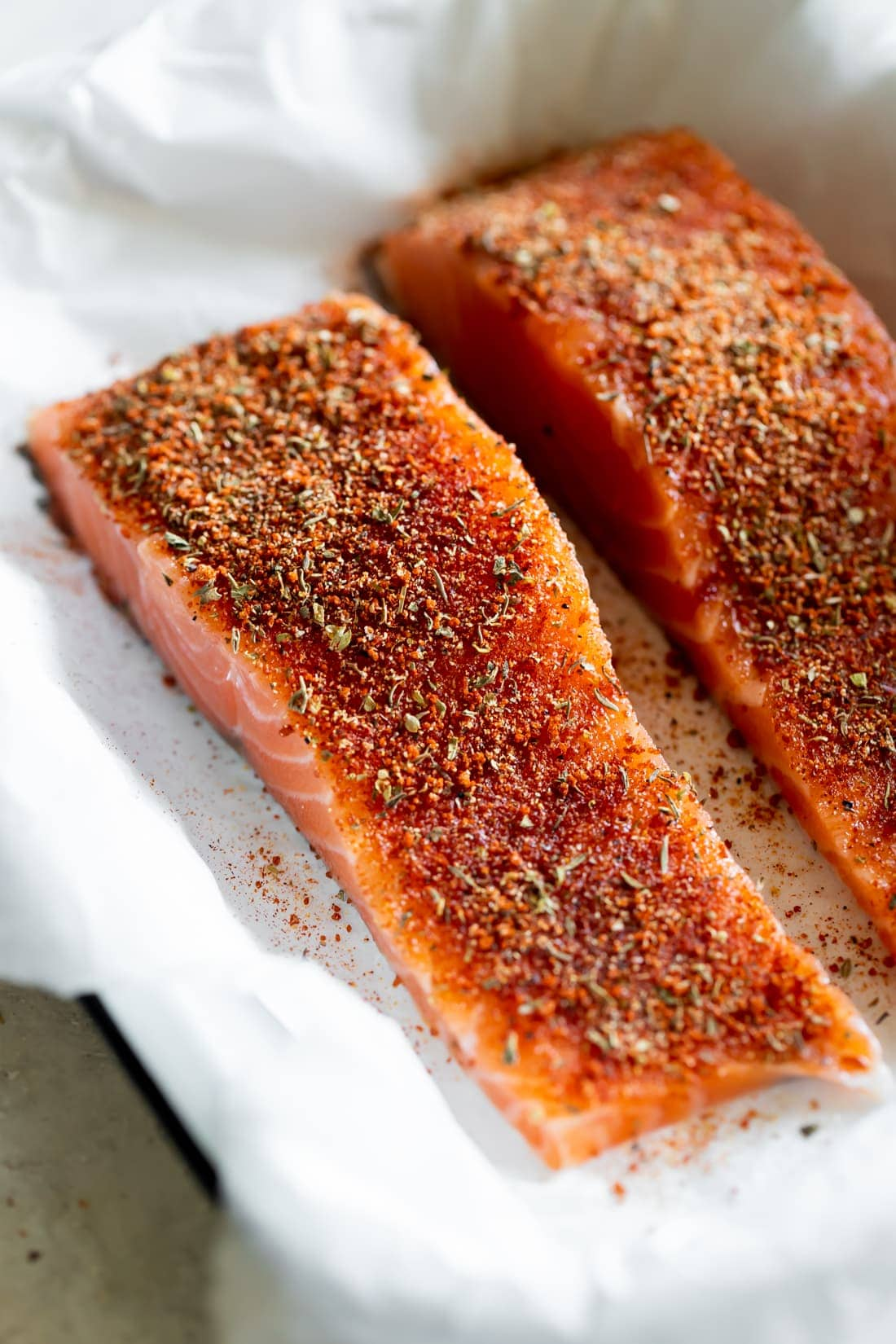 salmon with blackened seasoning on a white baking dish
