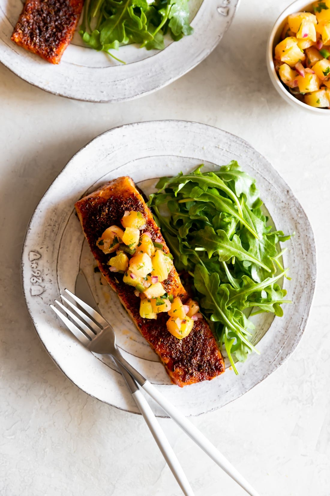 blackened salmon with pineapple jalapeno salsa on a white plate