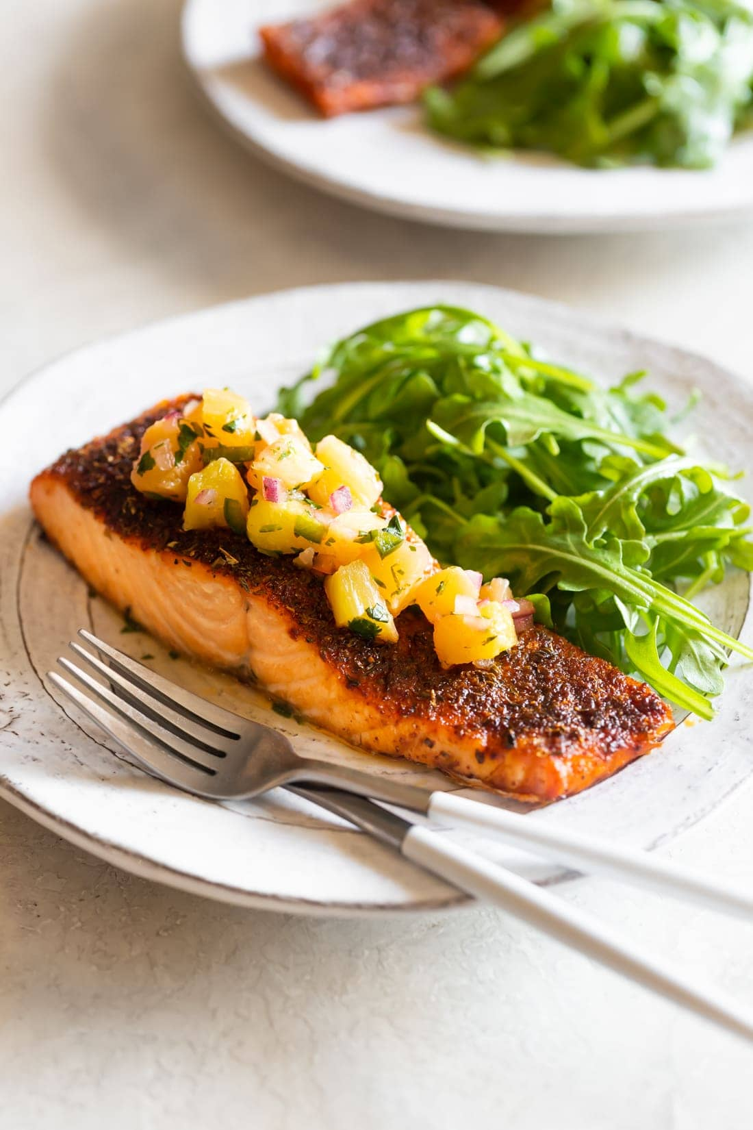 blackened salmon with pineapple jalapeno salsa on a white plate with arugula