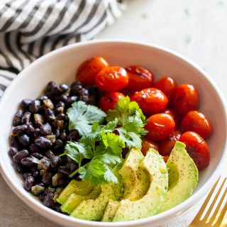 charred tomato salad bowl with sautéed black beans and sliced avocado
