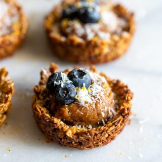 Granola cups made with oats, almonds and walnuts, filled with cashew butter caramel then topped with blueberries, shredded coconut, and lemon zest.