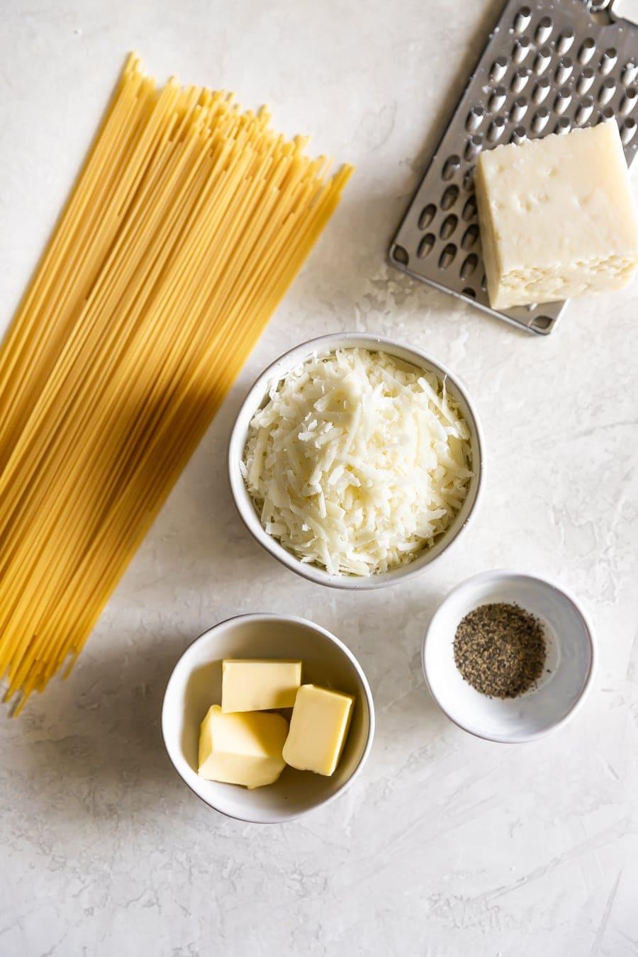 ingredient shot of cacio e pepe with Pecorino, pasta, black pepper, and butter