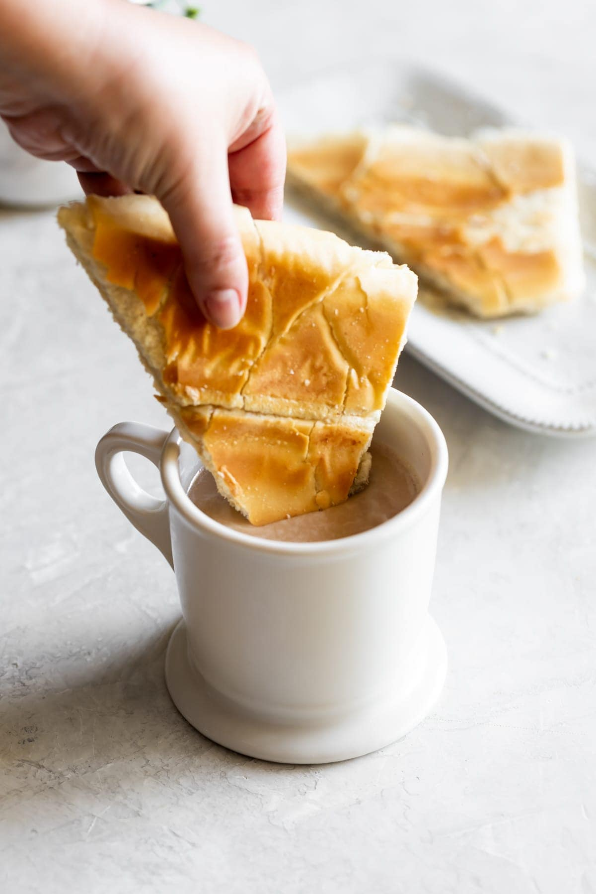Cuban toast being dipped into cafe con leche