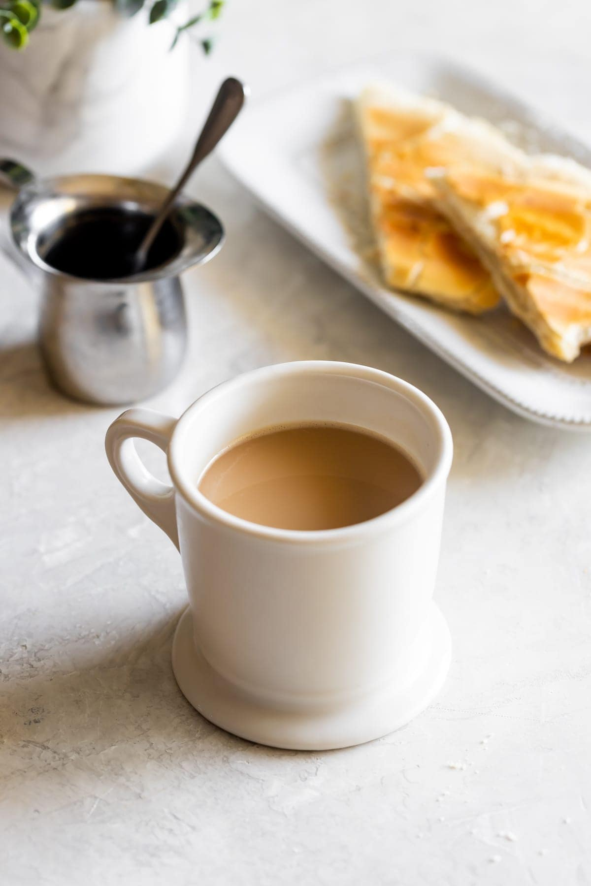 cup of cuban coffee with milk next to espresso cup and cuban toast