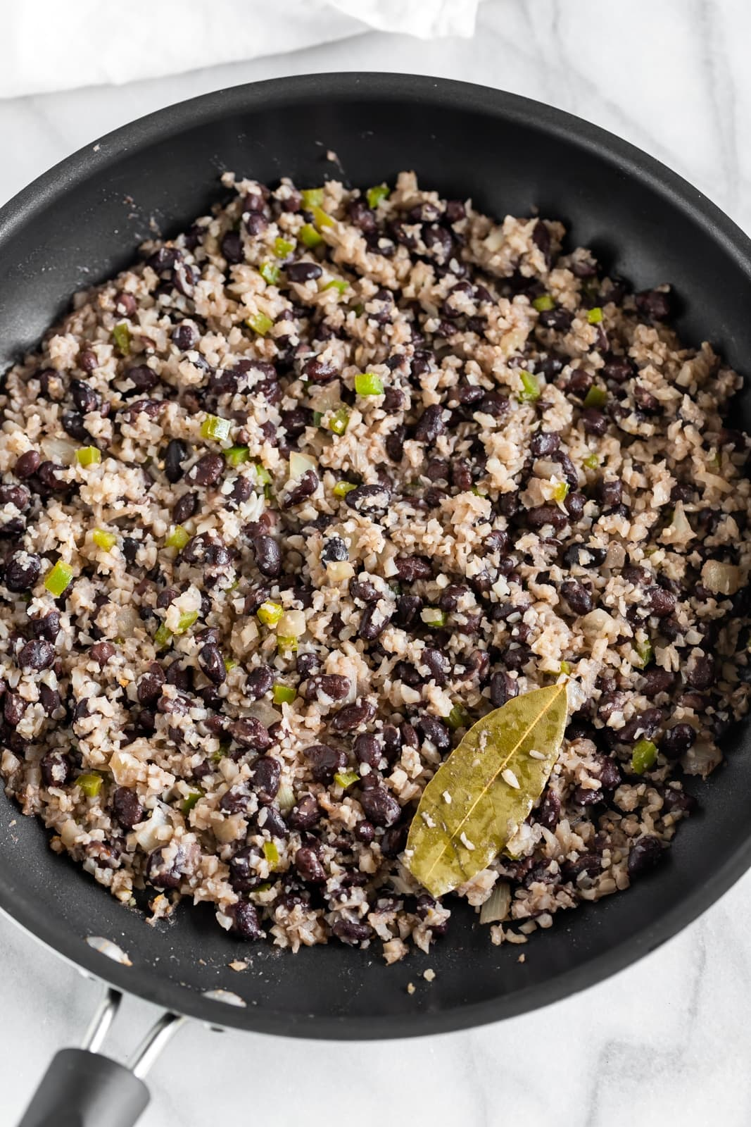 A healthy twist on the popular Cuban-style black beans and rice! A quick and easy weeknight dish made with riced cauliflower, cumin, oregano, and black beans. Pairs easily with salmon or chicken!