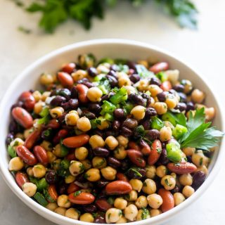 A plate with three bean salad tossed in chimichurri sauce