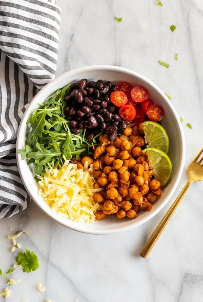 Vegetarian taco bowls made with spicy, smoky chipotle chickpeas, black beans, arugula, shredded cheese, and chopped cherry tomatoes!