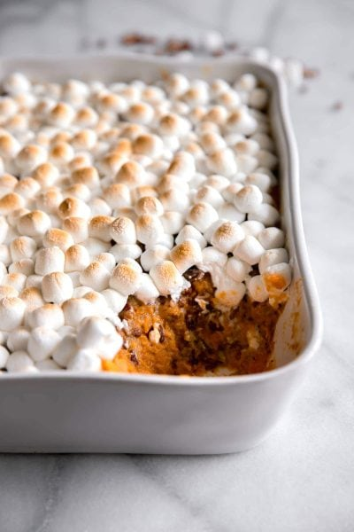 mashed sweet potato with toasted marshmallows on top in a casserole dish with a spoonful missing