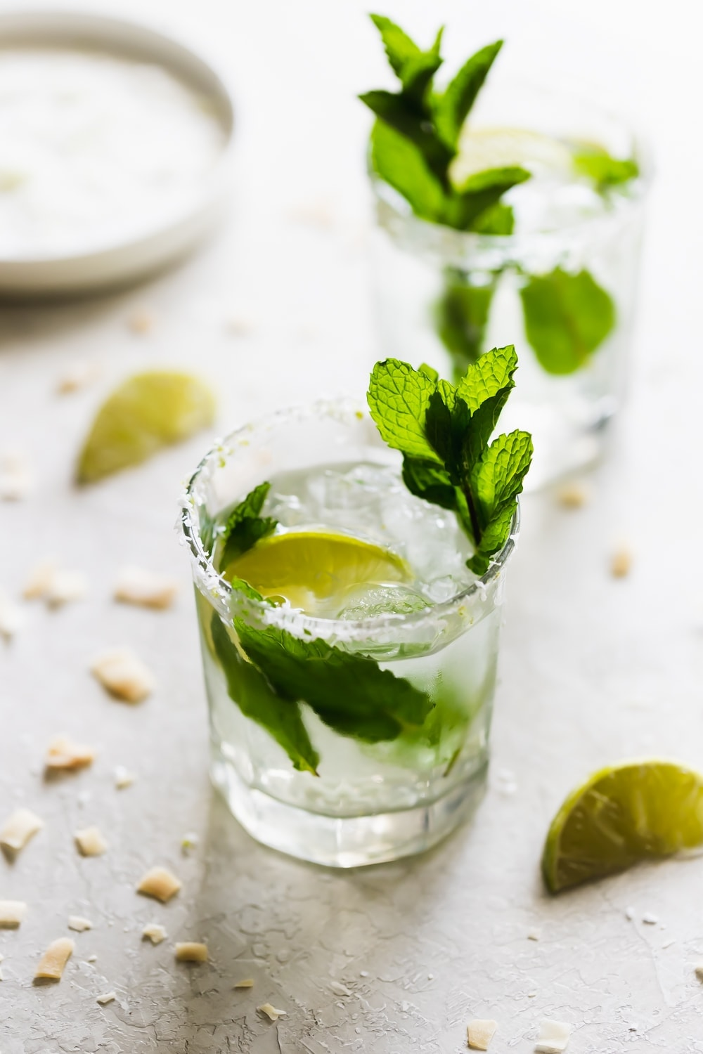 two glasses of coconut mojito drink with mint leaves and lime wedges