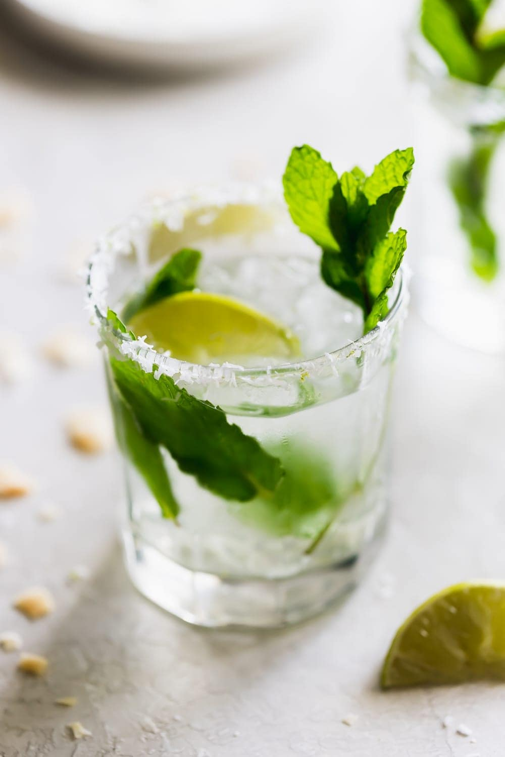 glass of coconut mojito drink with mint leaves and lime wedges