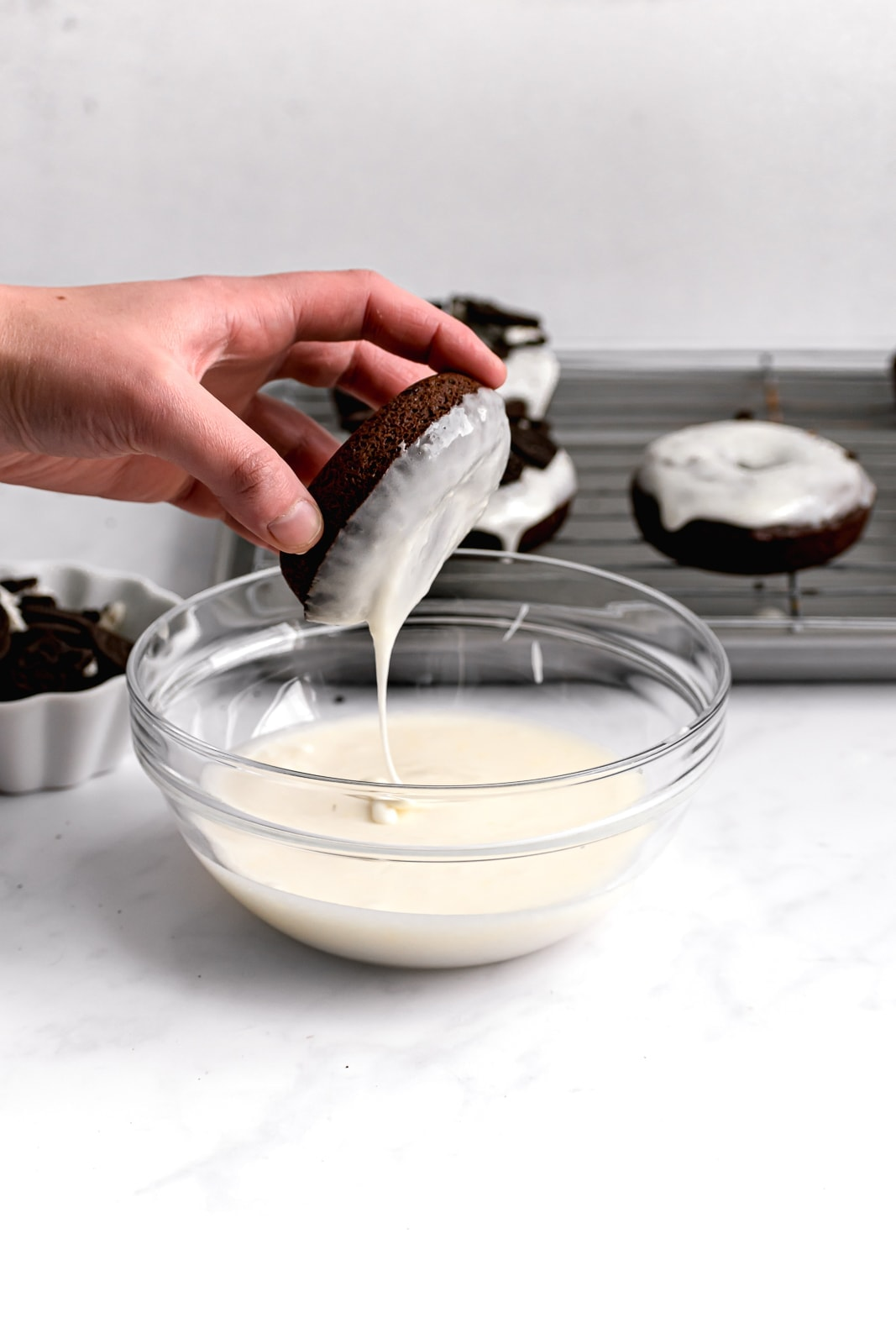 chocolate donuts being dipped in a thick cream cheese icing
