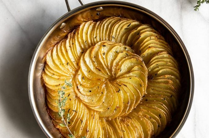 Thinly sliced gold potatoes tossed in garlic, butter, and thyme then roasted to perfection. An easy 5-ingredient side dish for any occasion!
