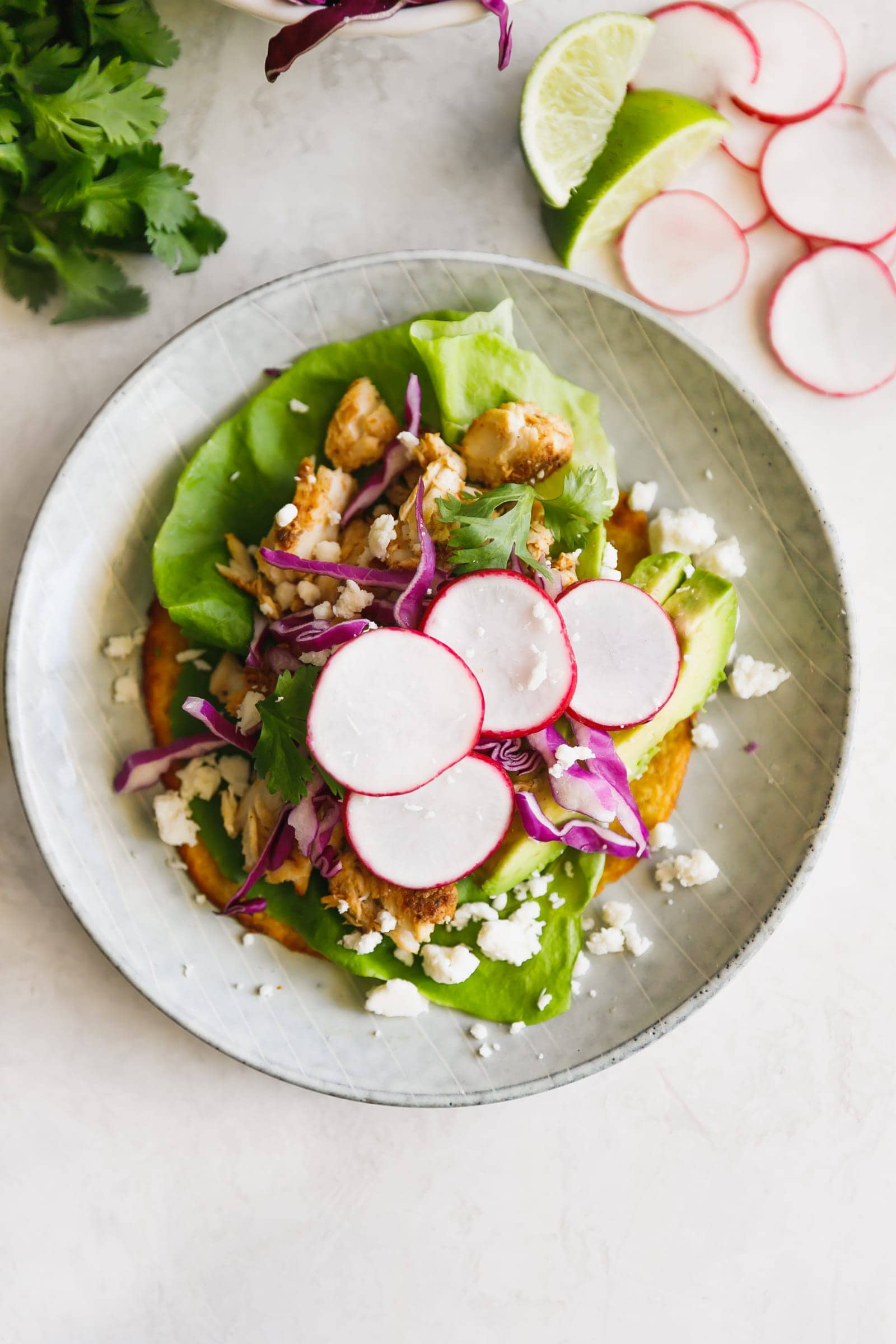 Flat, fried corn tortillas (aka tostadas) topped with butter lettuce, avocado, flaky white fish, red cabbage, jicama, radishes, cilantro and queso fresco!