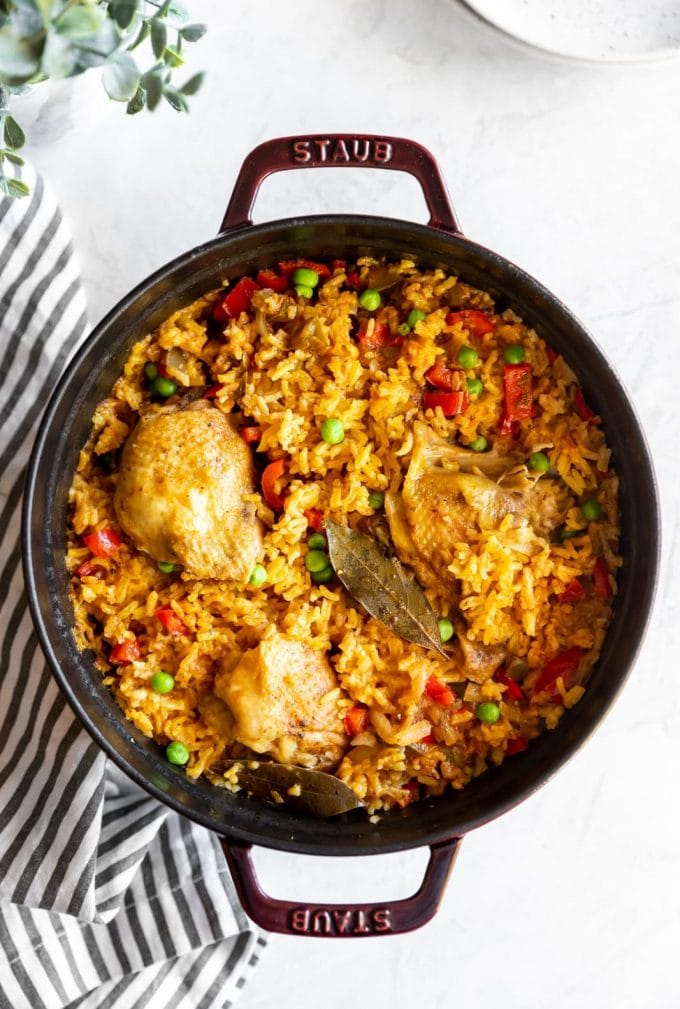 Staub dutch oven with cooked Cuban yellow rice with chicken (arroz con pollo)