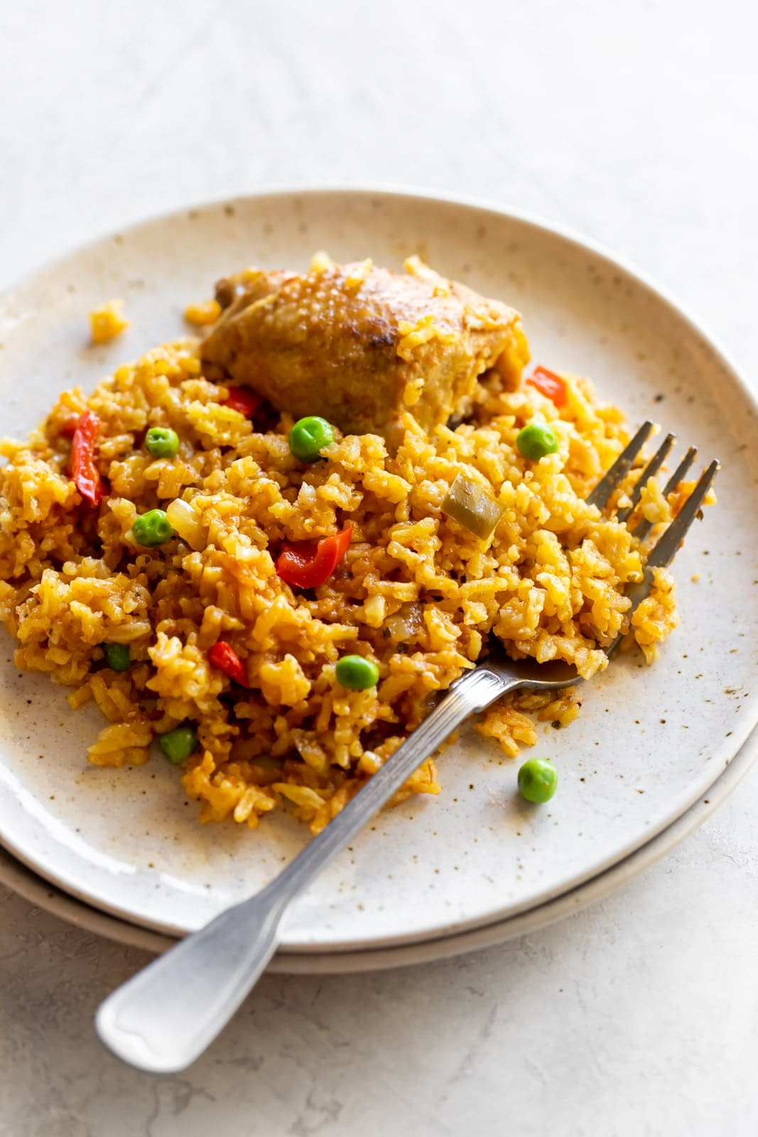 The best comfort food - arroz con pollo! Classic and authentic Cuban-style rice with chicken made with in one-pot with spices, tomato sauce, flavorful chicken thighs and fluffy yellow rice.