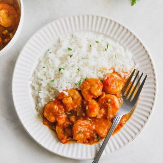 deviled shrimp on a white plate with white rice