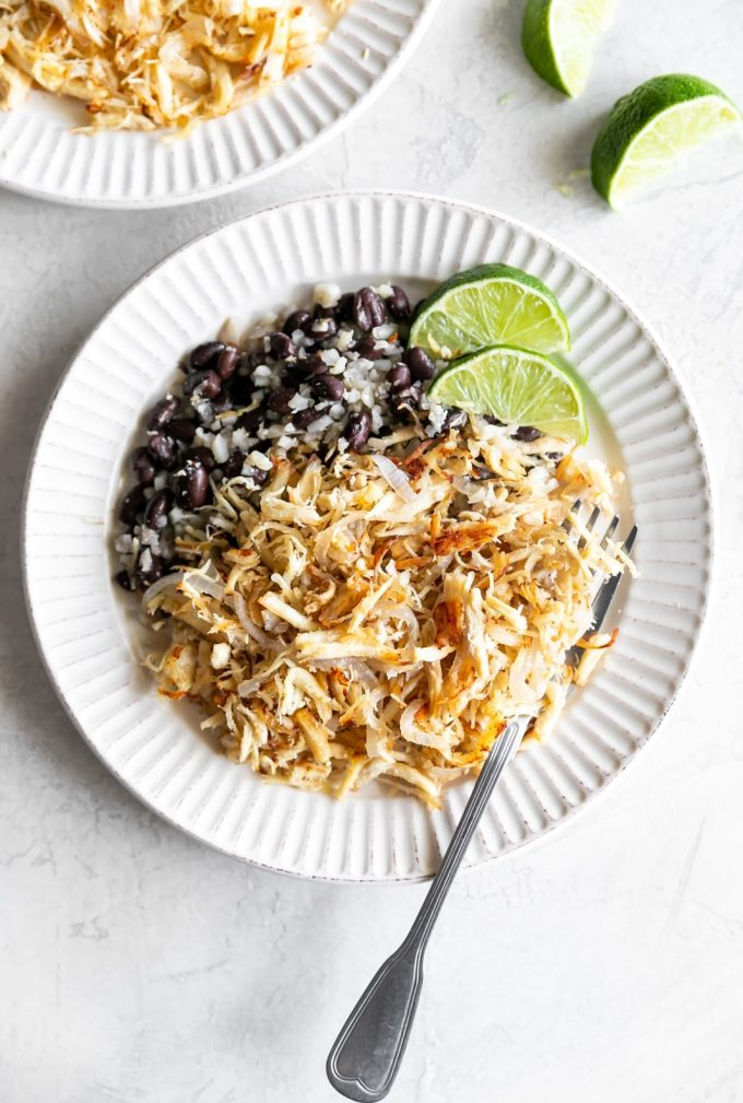 cuban shredded chicken with black beans and rice on a white plate