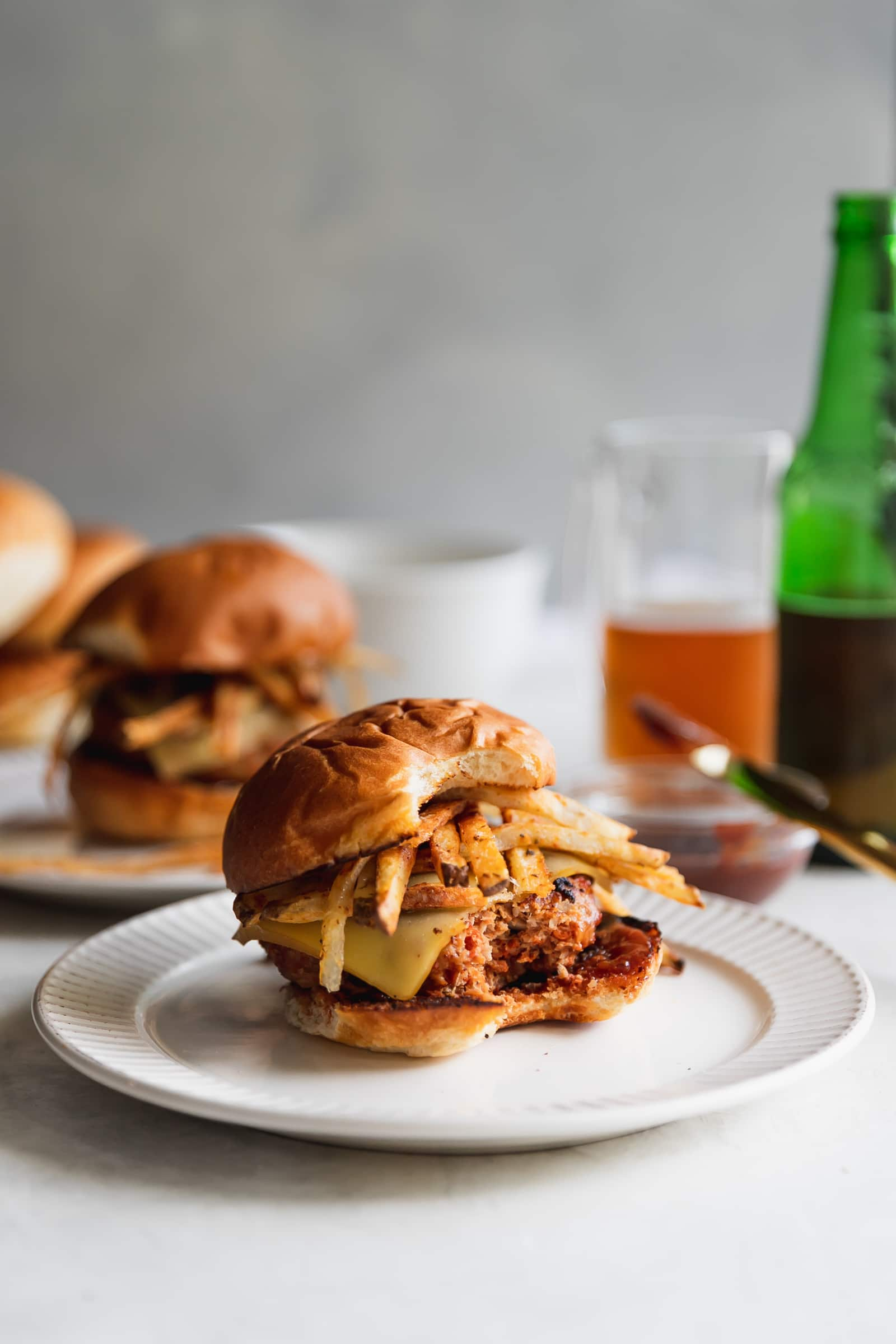 A Cuban-inspired burger made with ground turkey, chorizo, chopped onions, spices, melted gruyere, homemade shoestring potatoes, and guava BBQ sauce served on toasted hamburger buns.