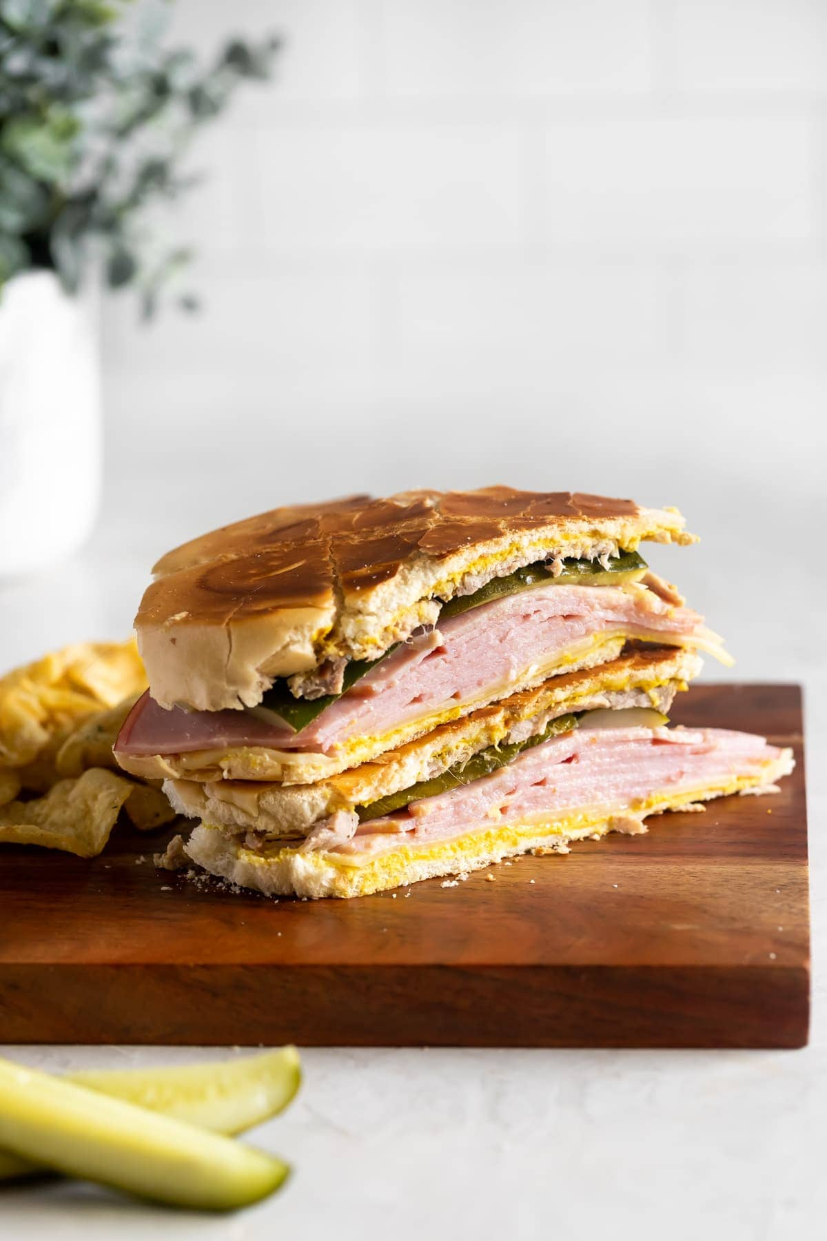 Cuban sandwich sliced in half on a cutting board with chips