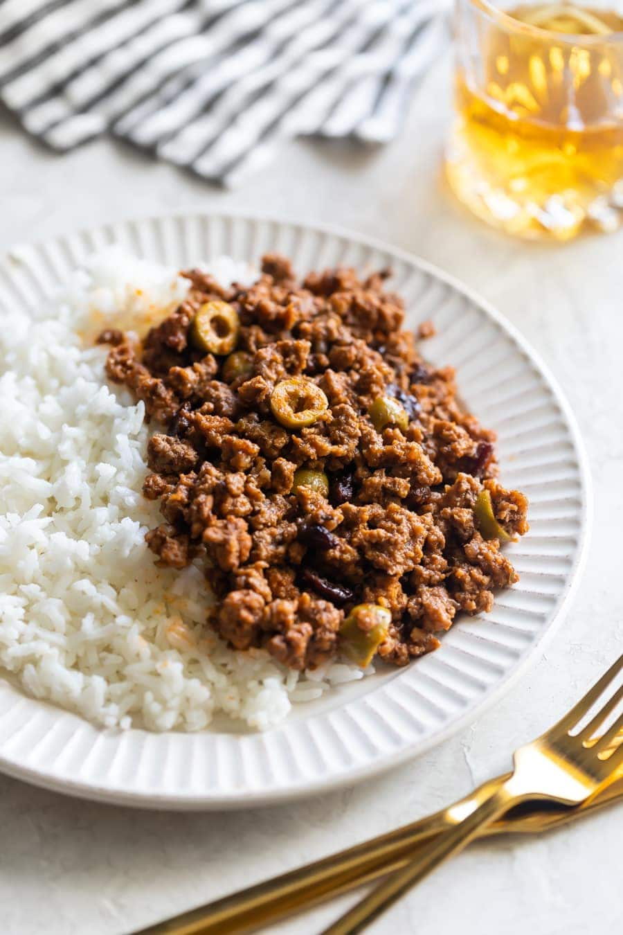 close up of cuban picadillo with white rice, gold fork and knife and a glass of wine