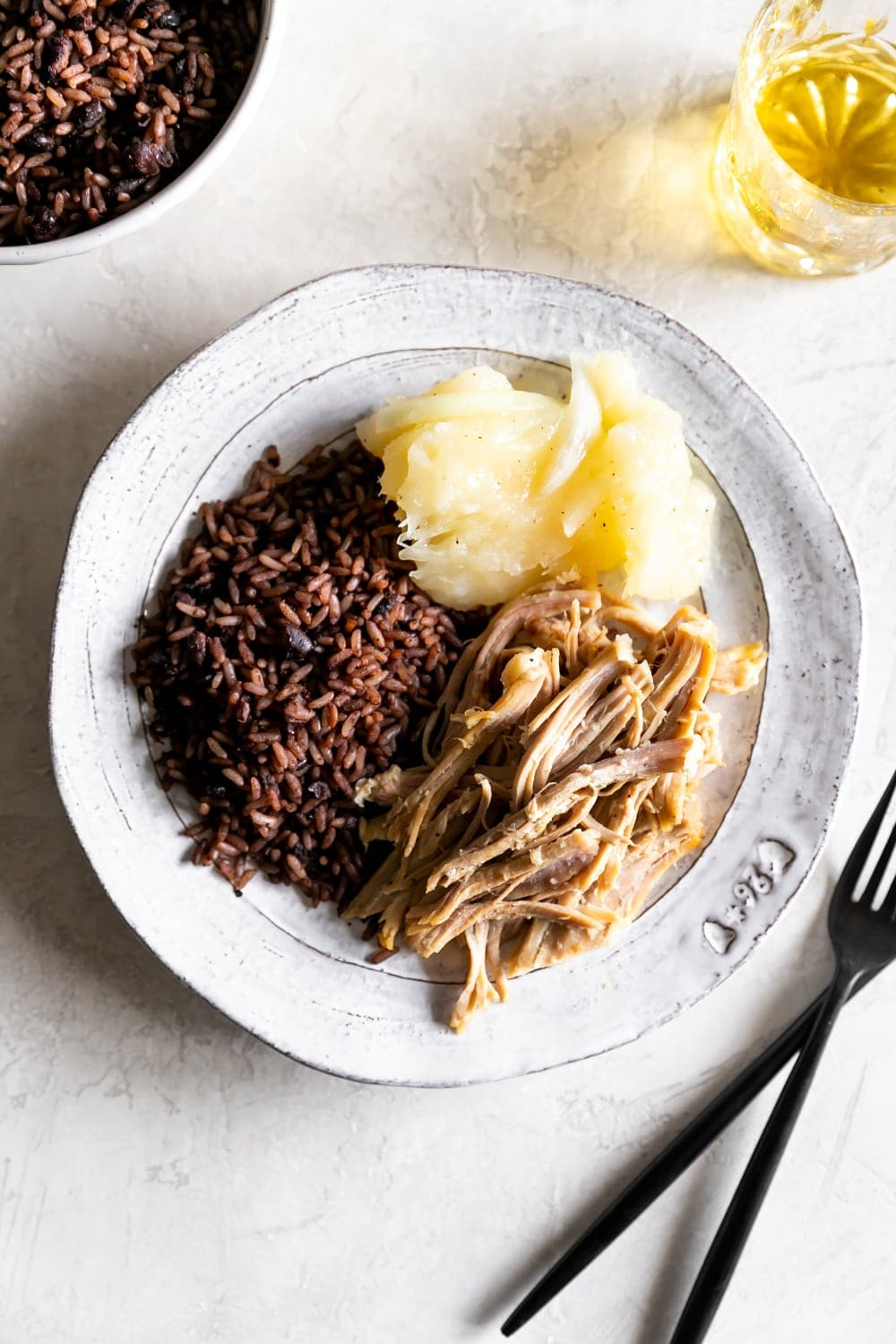 cuban roast pork, cuban arroz congri, yuca with mojo on a plate