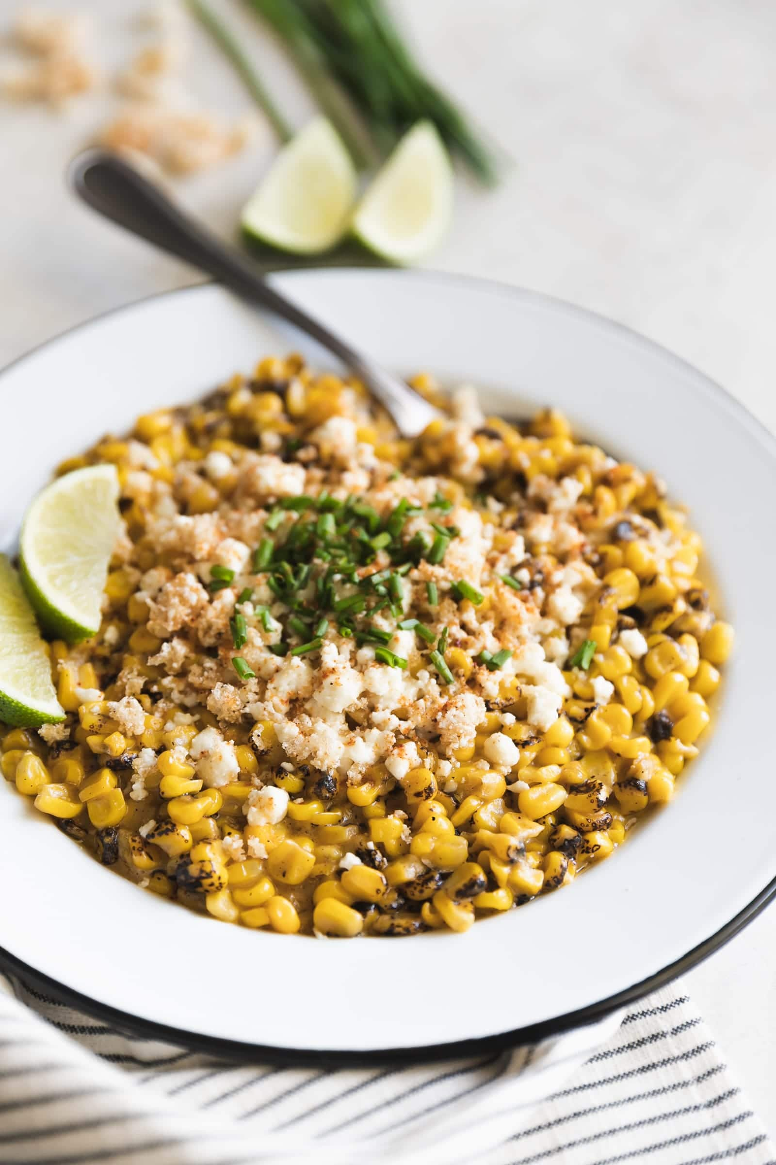 Easy Chipotle Mexican Street Corn. Fire roasted corn mixed with spicy chipotle mayo and mozzarella then topped with crushed pork rinds, crumbled cotija and chives.